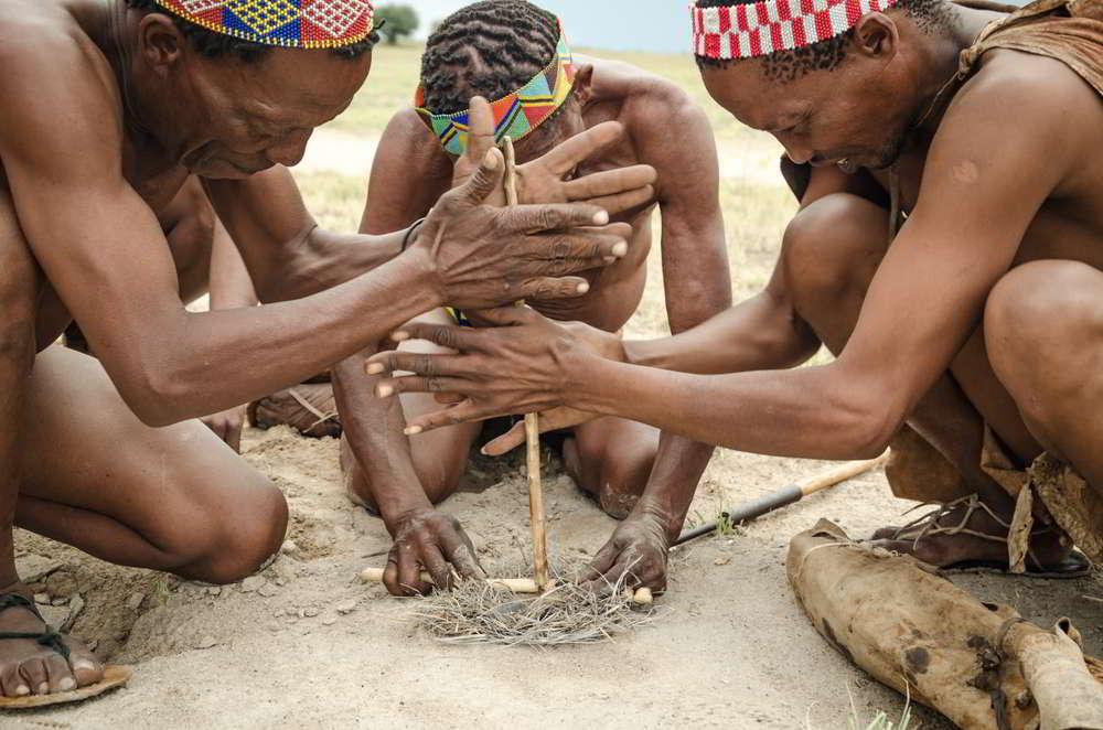 Tribesmen squatting and kneeling
